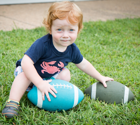 Child Holding Footballs